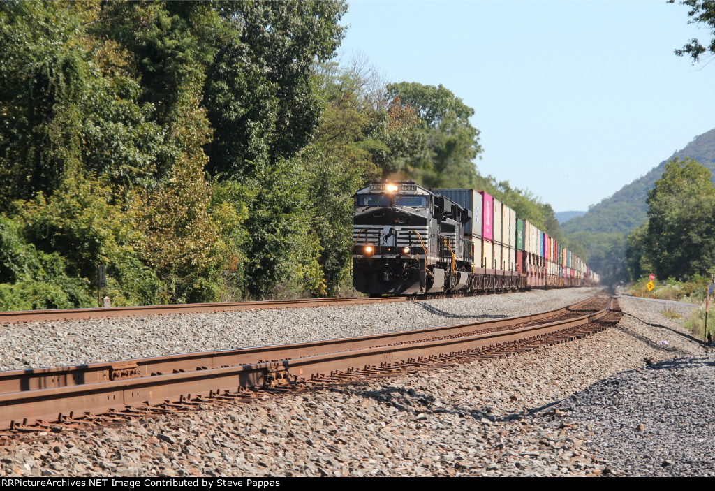 NS 7521 leads a container train through MP 116